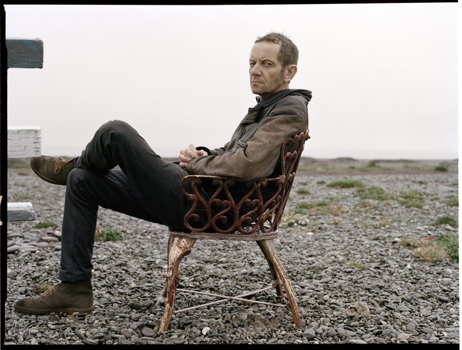 roy montgomery sitting legs crossed in a chair on a stoney beach with no sea