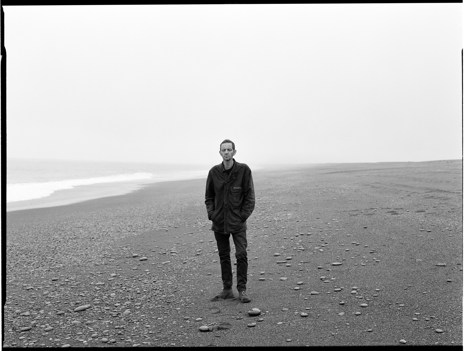 roy montgomery standing on a deserted stoney beach