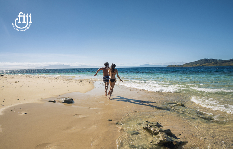 couple romping along waters edge on a golden sand beach in fiji with blue sky and ocean