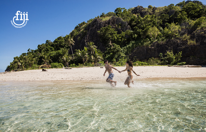 couple holding hands running through the c;ear water on a fijian beach