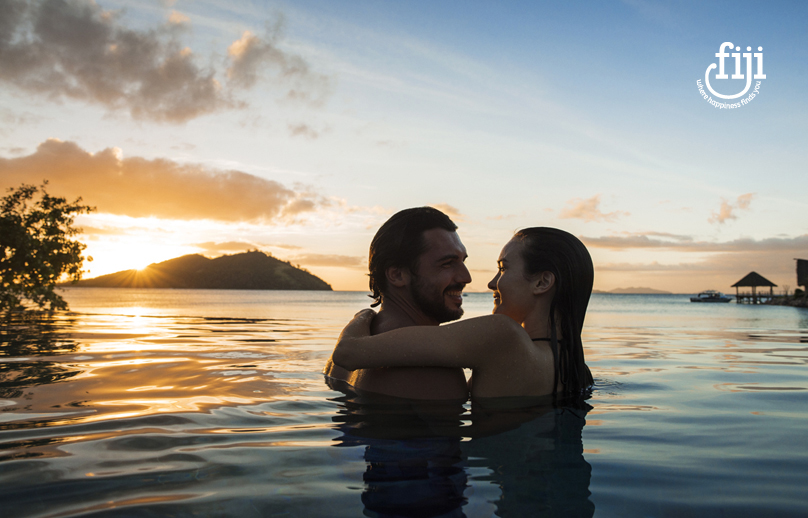 couple embracing in chest deep calm sea as the sun sets behind an island in fiji