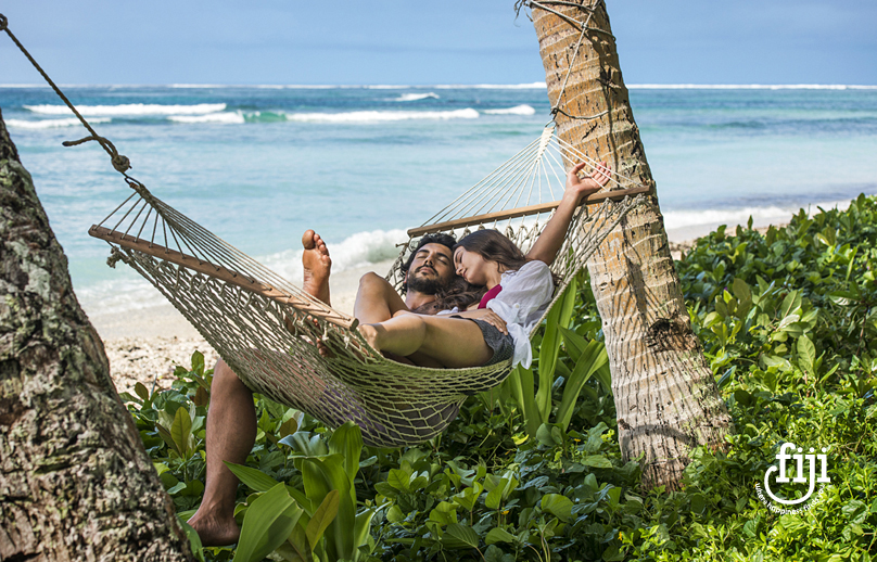 couple relaxing in a hammock between palm trees on fijian beach with blue sea