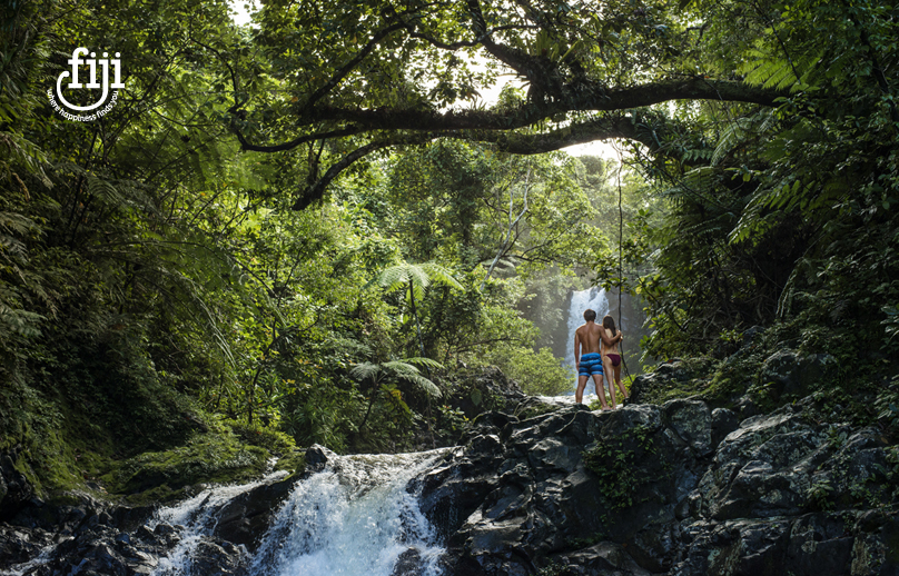 couple in fiji standing on rocks beside a waterfall surrounded by tropical forest