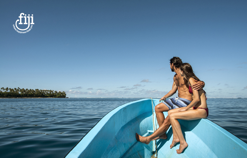 couple sitting on the side of a small open motor boat on calm ocean