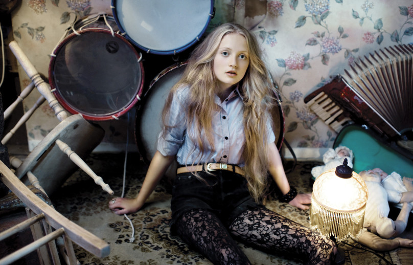 blonde girl sitting amongst upturned chairs, drum kit and accordian