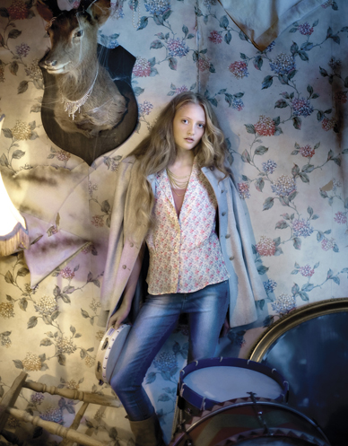 blonde girl in jeans standing under trophy head mounted on floral wallpaper covered wall