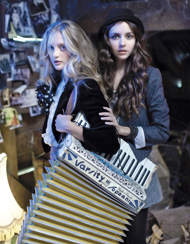 girl with long curly brunette hair resting her hand on the arm of blonde girl with an accordian hanging from sholder