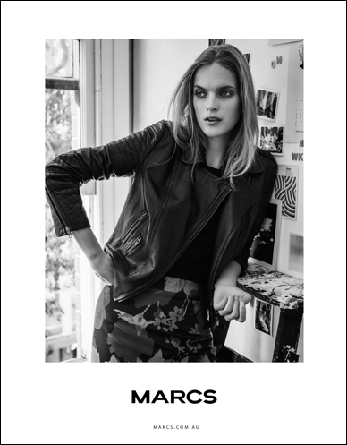 marcs blonde female model wearing leather jacket leaning against shelf