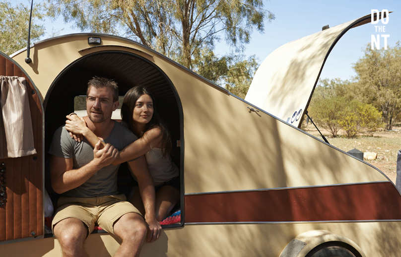 couple in the doorway of a brown vintage mini caravan on a sunny day parked under gum trees in the northern territory outback