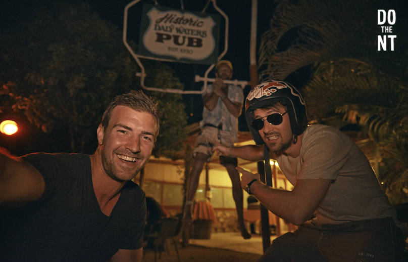 friends fooling around at night outside the daily waters pub in the northern territory