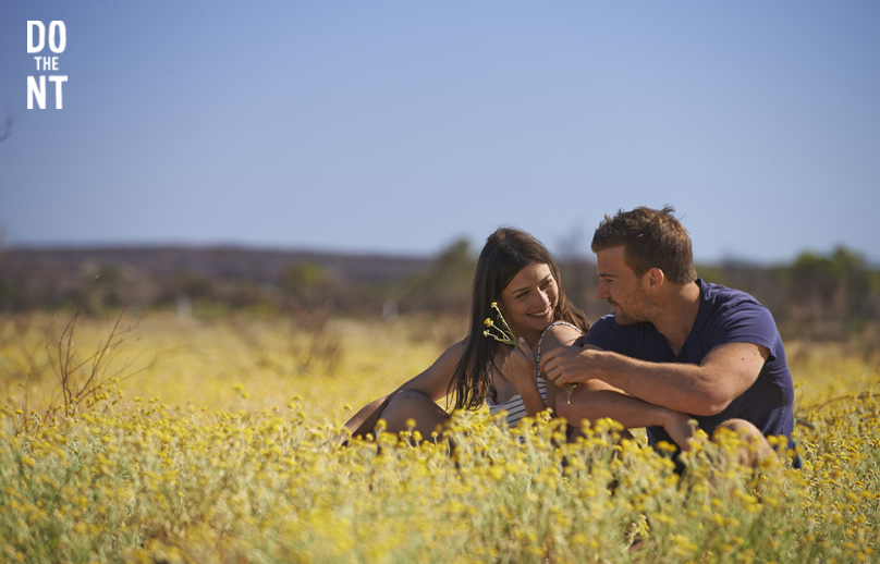 girl holding flowers smiling at boy as they sit amongst field of yellow wild flowers in the northern territory