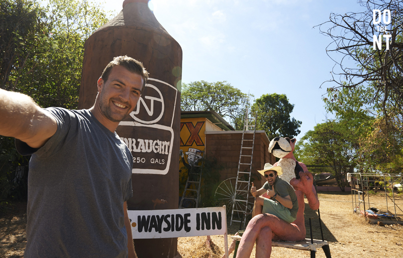 2 male friends and the big beer bottle and big pink panther outside the wayside inn in the northern territory