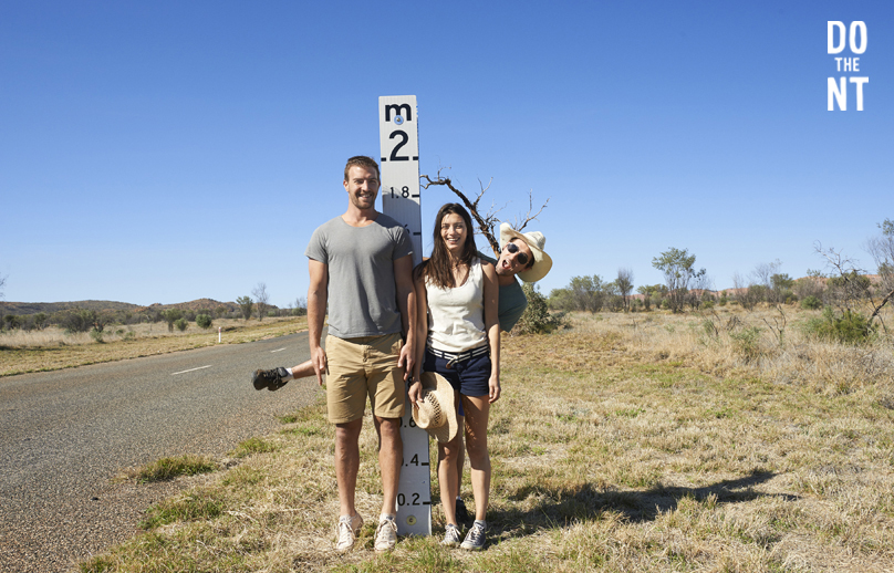 a couple an male friend standing in front of a 2m high flood level marker beside an outback northern territory road