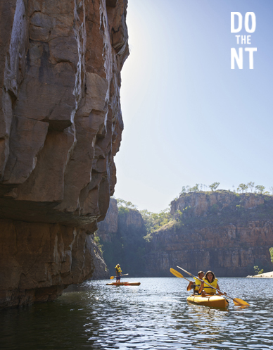 a double kyack and a paddle board in a northern territory canyon with sheer rock face