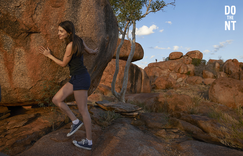 young woman embracing rock in ochre colored rocky northern territory outback