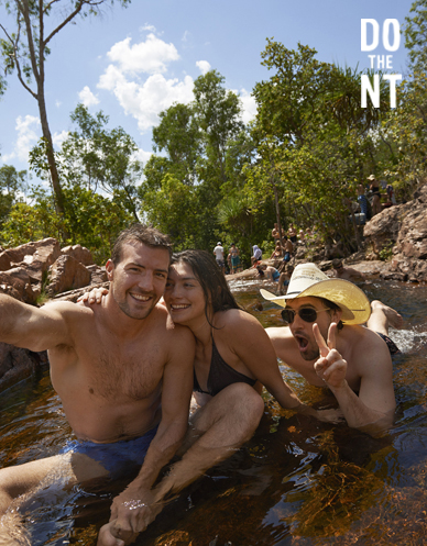 3 friends cooling off in shallow rocky northern territory stream