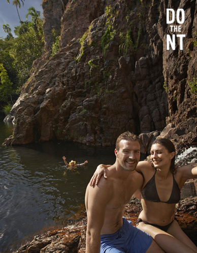 couple sitting on rocks above friend swimming in northern territory waterhole below them