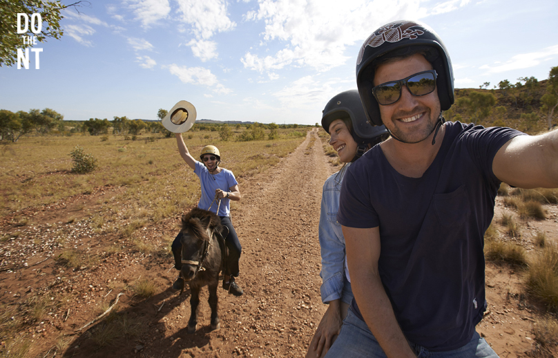 couple riding down a long and straight northern territory outback track with their friend riding a donkey behind them
